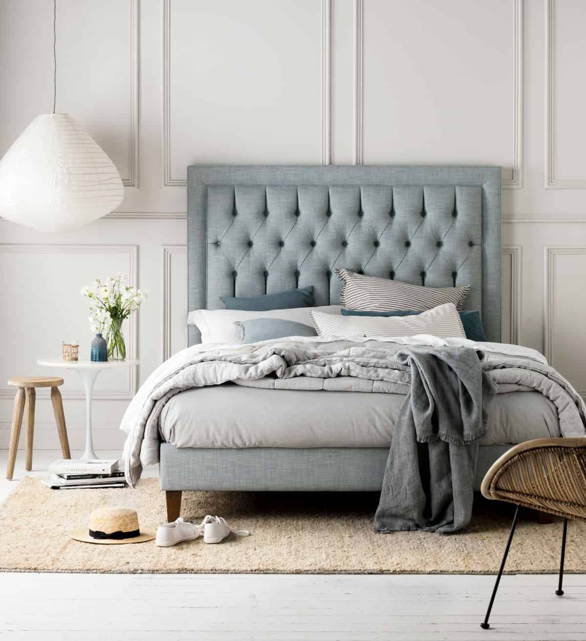 heatherly Design's Tilbury bedhead layered with bed linen and throws and shoes at the end of the bed