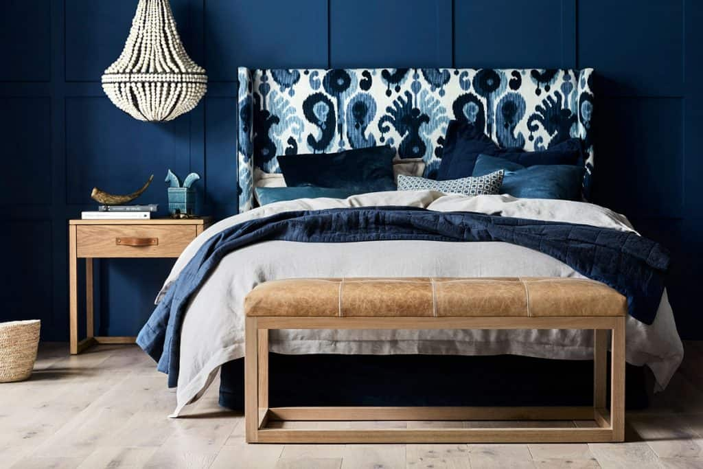 Heatherly Design's Sibelle bedhead in Blue Ikat Pattern fabric with the Mercer Footstolol in leather at end of bed